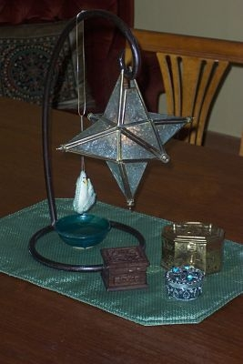 Star candle holder with three containers for Magi gifts, small bowl of water and dove