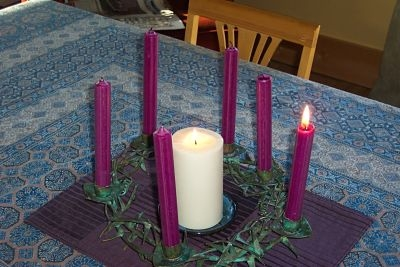 The lite Christ candle is surrounded by six purple candles, only one of which is lite.