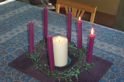 The lite Christ candle is surrounded by six purple candles, only two of which are lite