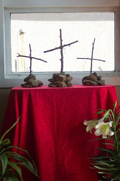 Three crosses stand on a small table covered with a red cloth