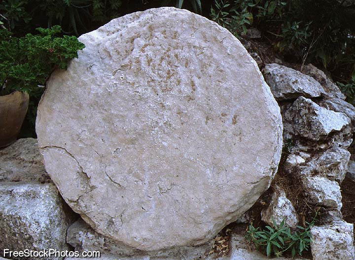 A tomb with a large round stone sealing it